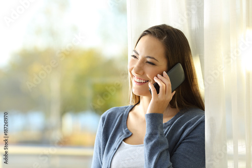 Foto op Canvas Snelle auto s Woman talking on phone standing at home