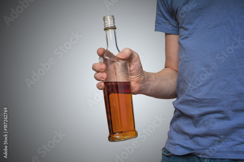 Alcoholic man is holding bottle with whiskey.