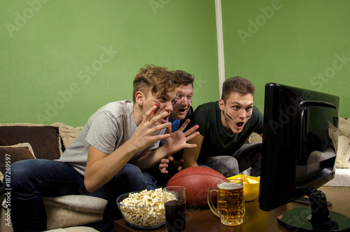 Fotobehang Voetbal Shocked group of people, family watching american football on television, funny concept