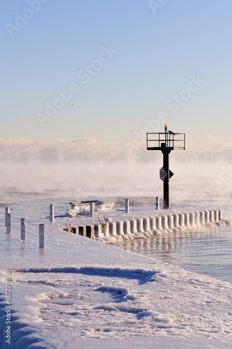 Ice coats a breakwater as vapor rises from the Lake Michigan waters as ice forms in Chicago's 31st Street Harbor. due to the bitter cold.