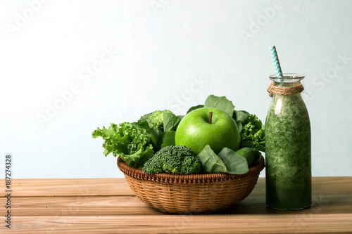 Fototapeta the Healthy fresh green smoothie juice in the glass bottle on wooden table with green apple and vegetables basket for healthy detox and diet habits concept
