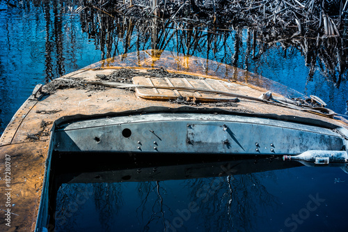 Foto op Canvas Schipbreuk Sunken orange boat on the river