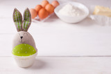 Easter bunny on a blurry background of ingredients for making festive eggs and Easter cakes. Copy space - 187290343