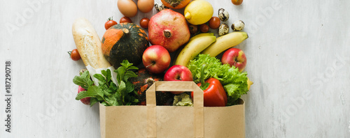 Paper bag of different health food on white wooden background