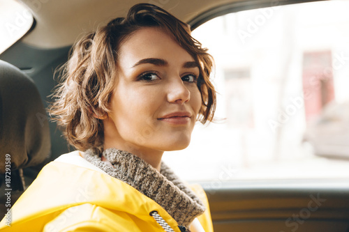 Pretty young lady dressed in raincoat sitting in car.