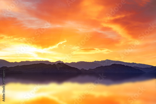 Fotobehang Oranje eclat scenic dawn on a mountain range reflecting in water