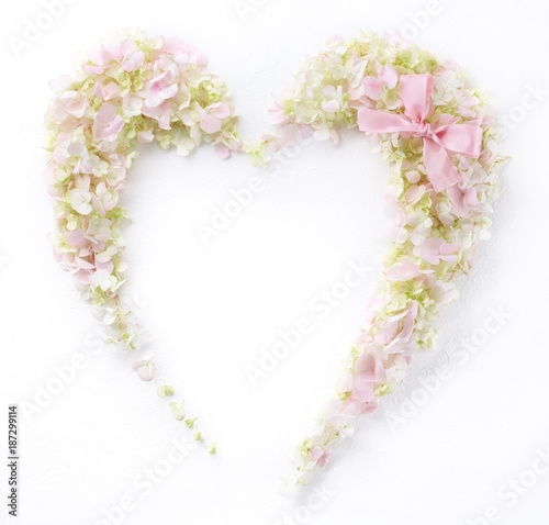 Heart symbol made of flower petals with gift ribbon bow,Flat lay.