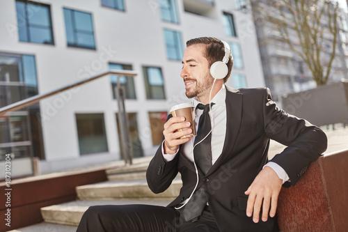 Lächelnder Geschäftsmann trinkt einen Kaffee
