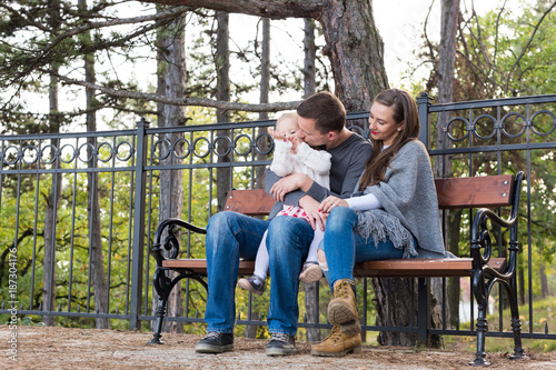 Happy family of three sitting on a bench in a park enjoying their time together. Father giving a kiss to his toddler daughter, mother smiling.