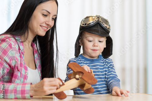 Mother and son are playing with wooden plane.