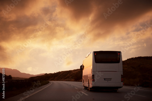 Fototapeta White bus driving on road towards the setting sun