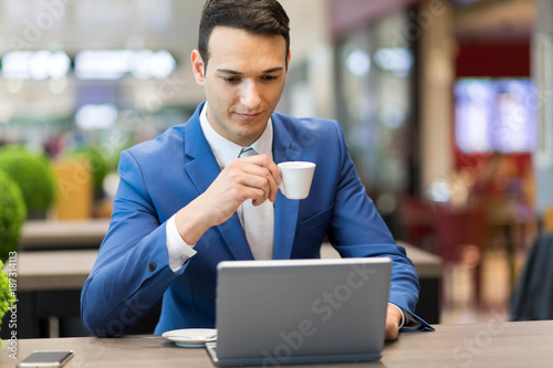 Businessman having a coffee while morking at his laptop