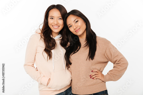 Two asian pretty cheerful ladies sisters