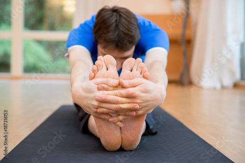 Obraz na płótnie Man practicing yoga indoors in a retreat space doing Seated Forward Bend Pose - Paschimottanasana - closeup of the hands