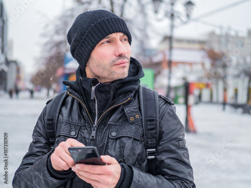 Tourist man looking for th place in GPS application in his smartphone.