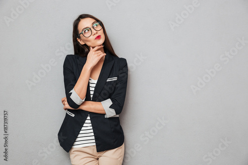 Poster Hoogte schaal Picture of Pensive asian business woman in eyeglasses looking up