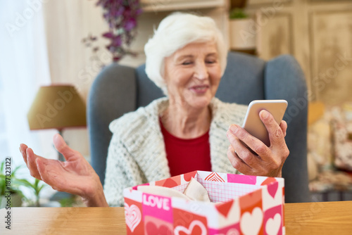 Foto Murales Cheerful senior woman holding modern smartphone received as Christmas present in hand while sitting on cozy armchair, interior of stylish living room on background