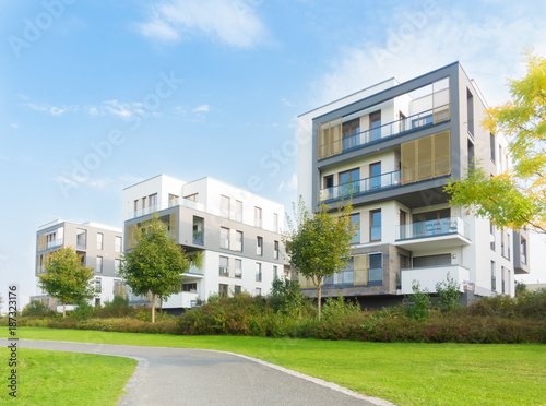 Leinwanddruck Bild Neubausiedlung und Fußweg in einer Parkanlage