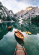 Leinwandbild Motiv Boats and slip construction in Braies lake with crystal water in background of Seekofel mountain in Dolomites in morning, Italy Pragser Wildsee