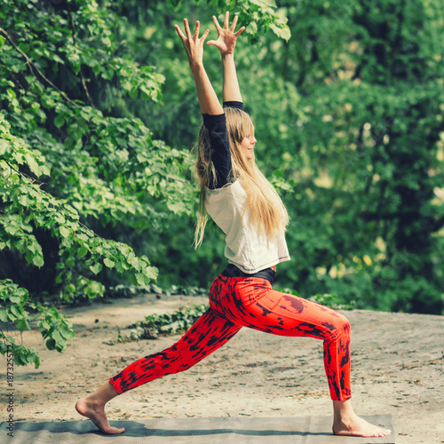 Wall mural Attractive blond woman doing yoga outdoors