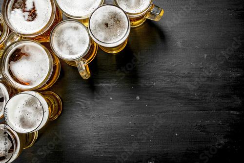 Fototapeta Glasses with beer. On black chalkboard.