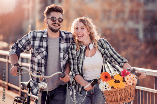 Young couple going for a bike ride on a sunny day in the city. - 187330348
