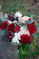Romantic arrangement of red and white summer flowers with roses and dahlias on stones