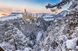 Neuschwanstein Castle during sunrise in winter landscape.
