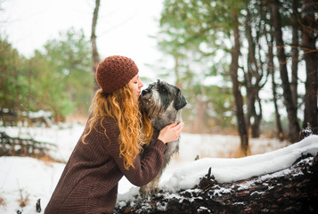 curly haired red-haired girl on a walk with a dog schnauzer in the winter afternoon in the forest