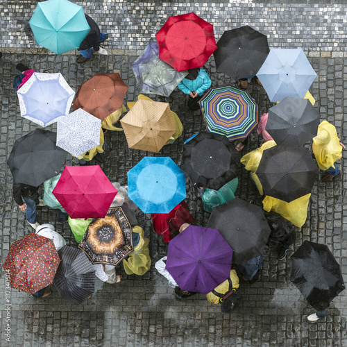 people with wet umbrellas photographed from a tower