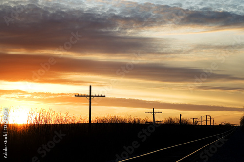 In de dag Spoorlijn Railway next to the old telephone poles at sunset