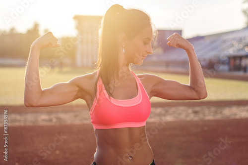 Fotobehang Fitness Fitness woman on stadium showing off muscular arms flexing biceps.