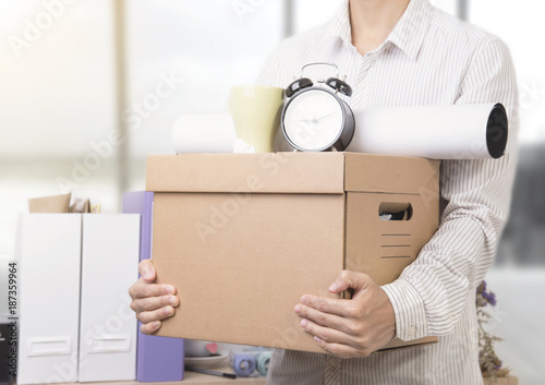 Foto Murales businessman holding personal items box ready moving leaving company. concept layoffs.