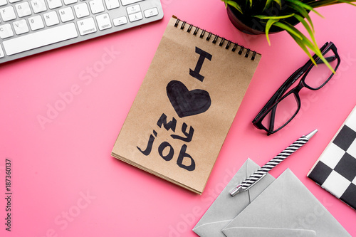 Find dream job. Handwritten motto I love my job in notebook on office desk on pink background top view copyspace