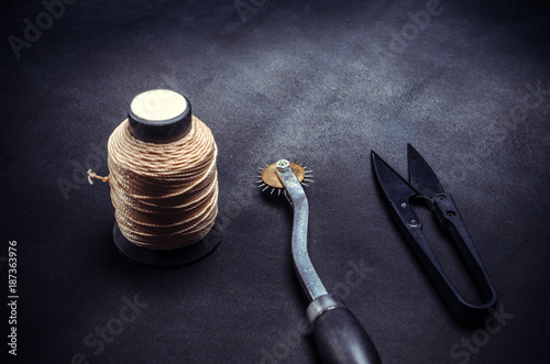 spool of yellow threads and tools on black background
