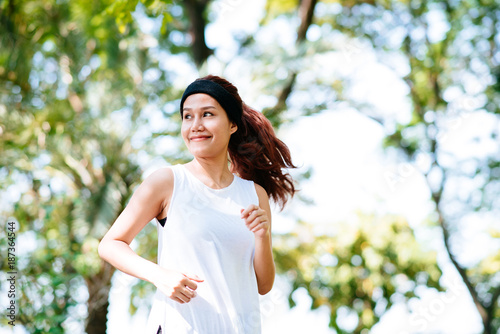 In de dag Jogging Beautiful happy young healthy Asian woman running in the park under the morning sunlight