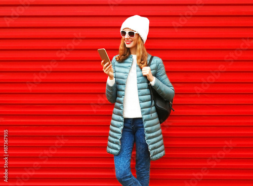Fashion smiling woman is using smartphone on red background - 187367935