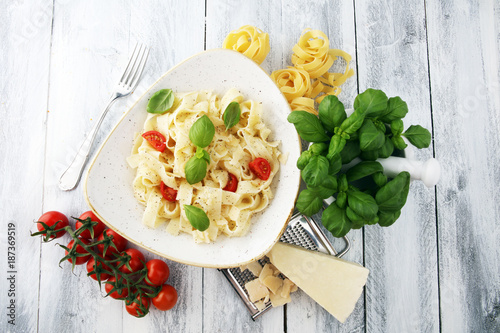 fettucine pasta white cream sauce with tomato and basil in white plate - Italian food style - 187369519