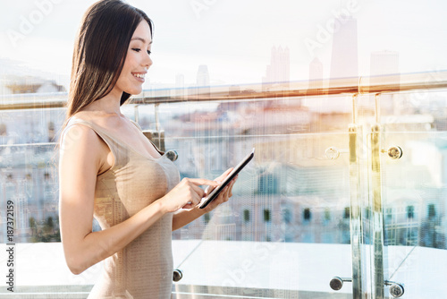 Young beauty. Cheerful female keeping smile on her face and looking at tablet while standing in semi position