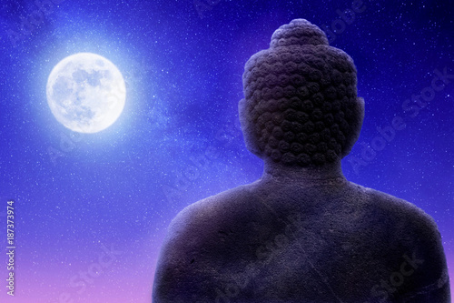 Fotobehang Boeddha Sculpture of Buddha on a night sky background and moon. Artistic image. Buddhism concept.