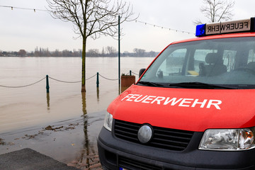 Fire department car on the flooded shore of a river