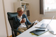 shoot of elderly woman working in her home office.