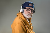 Calm pensioner wearing trendy clothing and headphones. Isolated on grey background - 187379705