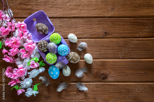Painted Easter eggs with feathers and a branch of sakura on a dark wooden background - 187382142