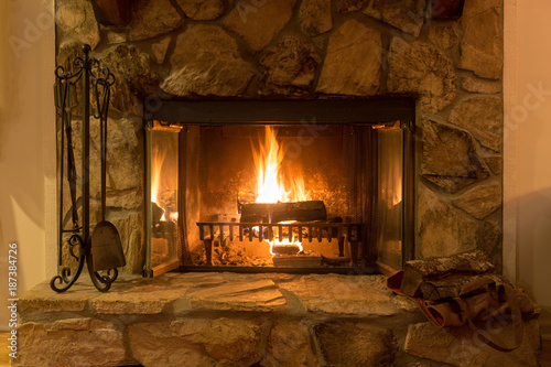 Intimate fire in a stone fireplace - 187384726