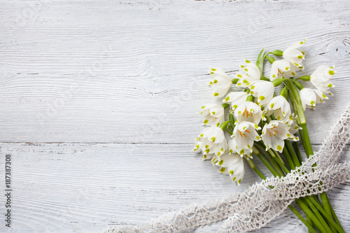 Snowdrop bouquet on a wooden background and lace ribbon - 187387308