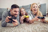 Family playing video games at home - 187395524