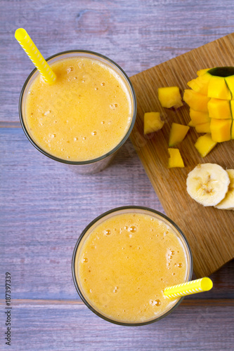 Foto op Canvas Milkshake Mango banana smoothie on wooden background. View from above, top, horizontal