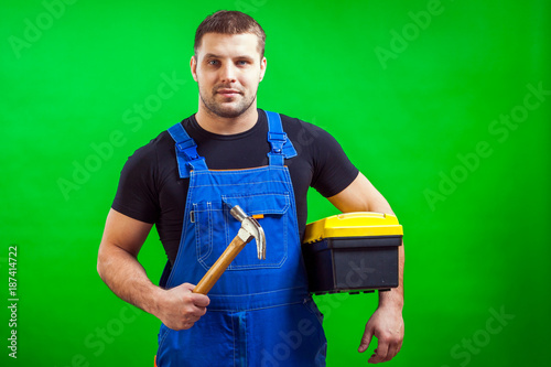 A dark-haired male construction worker in a black T-shirt and blue construction overall holds a wooden hammer and a box with construction tools on a green isolated background