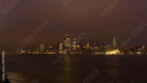 Tuinposter Chocoladebruin Panorama of Manhattan across Hudson River at night, New York City. Brightly lit New York skyscrapers during winter holiday season.